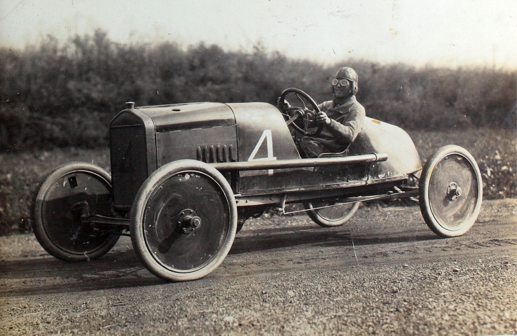 old sepia photo of a smiling racecar driver
