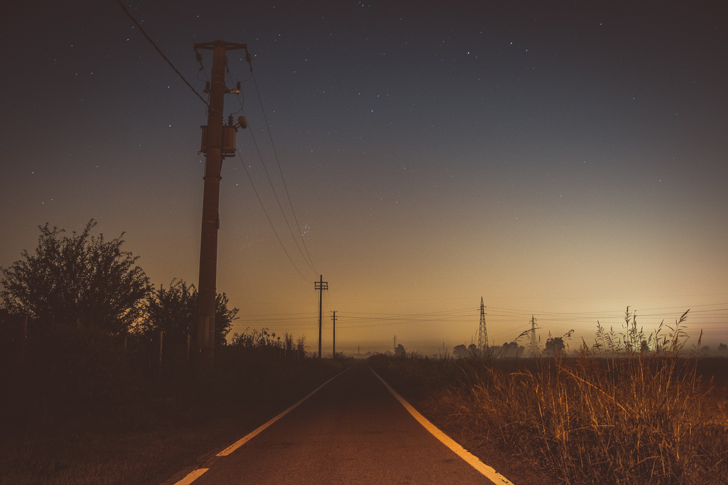 starry sky above a road at night